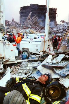 "September 11, 2001: Exhausted firefighter SLEEPING in a pile of rubble. ""This is a picture that immediately carries me back to those days when, caked in dust, we worked 24-hour shifts, smelled of wet concrete and death and had world wariness for the first time in our lives."" -Spencer Platt, staff photographer, Getty Images (Photo: Chris Hondros)"