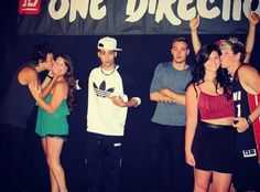 This picture. Harry is giving that girl a smooch, while Zayn awkwardly touches her back and makes an Oh! face. Liam is just chilling. Niall and that girl look like a couple and Louis is giving thr thumbs up of approval.