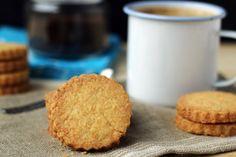 150g mąki pszennej     55g wiórków kokosowych     75g drobnego cukru do wypieków     150g niesolonego masła, pokrojonego  Wykonanie:  Mąkę wymieszaj z wiórkami kokosowymi oraz cukrem. Dodaj pokrojone masło i przesiekaj nożem lub siekaczem do kruchego ciasta. Wyrób gładkie, jednolite ciasto*.  Ciasto rozwałkuj na blacie lub stolnicy lekko oprószonej mąką na grubość około 5mm. Wycinaj ciasteczka okrągłą foremką o średnicy 5cm i karbowanym brzegu (lub inną, ulubioną foremką) i układaj ...