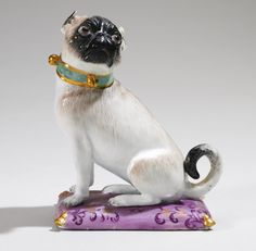 A MEISSEN FIGURE OF A PUG DOG CIRCA 1743 modelled by J. J. Kändler, seated to the left with naturally coloured brown coat and black muzzle, wearing a green collar with gilt bells and a rosette, on a rectangular gilt-tasselled puce cushion with puce and gilt foliate scrolls (minor chips and restoration)