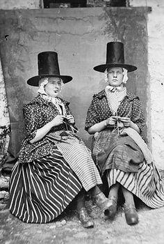 Two Welsh women in traditional dress knitting wool