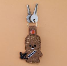 """Chewy Chewbacca Star Wars Inspired Keychain Fob    TO BUY: Shop directly at DynamicCrumbs.etsy.com  Price: $5.00.    """"May the Force be with you!"""" Love Star Wars? Do you know all the lines by heart? Well now you can be a part of the action! Keep your favorite Star Wars characters close to you! Fight the power of the Dark Side with Chewbacca!     This key chain is made of felt and you won't have to worry about it breaking from being bent or dropped. Kid and accident proof.    Products are…"""