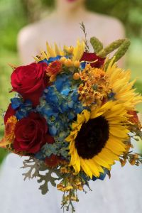 this beautiful fall bridal bouquet has lovely fall colors.like reds, blues, oranges and yellows. This wedding bouquet has roses,hydrangea, sunflowers, wax flower, chrysanthemums spider mums, and millet. Indian Summer by Enchanted Florist in Taos, New Mexico. http://www.taosflorist.com/weddings/taos-wedding-flowers/ fall wedding bouquets