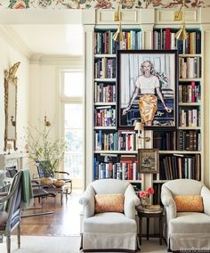 Art in front of bookshelf and that gold mirror