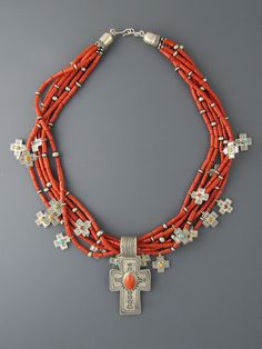 Six strands of gorgeous Mediterranean red Coral tubes embelished with 21 sterling silver cross charms set with assorted stones and a large Coral cross pendant at the bottom. Once this is gone there will not be another one. Overall length 26 inches.
