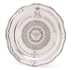 A FINE AND IMPORTANT FABERGÉ SILVER PRESENTATION SALVER, MOSCOW CIRCA 1900. With scalloped rim and edged with reeded ribbon-tied border, the cavetto engraved with the Imperial Double Headed-Eagle, surrounded by scrolling foliage on a matted ground. Engraved with the Imperial cipher of Nicholas II and Cyrillic dedicatory inscription, To His Imperial Majesty Nicholas II from Kirasirsky His Majesty Guard Regiment - Peterhoff June 20 1909, also engraved with the Regimental Badge.