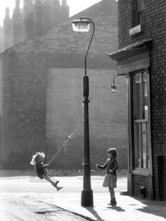 Two girls swing on a lampost, Manchester, 1965, by Shirley Baker