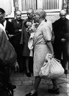 A woman collaborator and her baby, whose father is German, returns to her home after having her head shaven following the capture of Chartres by the Allies. (Photo by Robert Capa/Getty Images). 1944