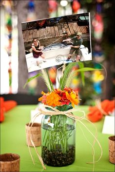 I don't like the details here; dark stones, twine ribbon, and orange and green color scheme. But this could work with photo (s), flowers, mason jar with a number etched on the side? Jar Centerpieces, Wedding Centerpieces, Wedding Decorations, Table Decorations, Cute Wedding Ideas, Wedding With Kids, Wedding Fun, Wedding Rehearsal, Rehearsal Dinners