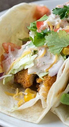 Crispy Southern-Style Chicken Strips topped with shredded lettuce, diced tomatoes, red onions, sweet corn, Mexican shredded cheese and a creamy salsa ranch dressing on a warm flour tortilla.