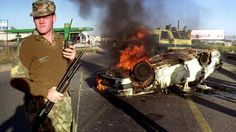 A South African policeman stands  near a burning car outside Soweto (19 April 1993)