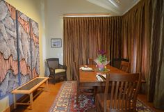 Dining room drapes drawn for privacy and emphasis of artwork lit from ceiling