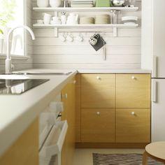 Moderne IKEA køkken med lyst træmønster og hvide bordplader, hvidt blandingsbatteri og hvide væghylder