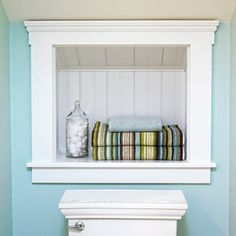 Tucked between wall studs and just below the eaves, a beadboard-lined, trimmed-out cubby provides a perfect spot for extra towels in a diminutive powder room.