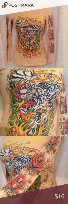 Peach Ed Hardy Tiger Tee Medium Christian Audigier Bold, chilling tiger and flames by Ed Hardy on a light peach background.  Shows rendering with and without color.  Sleeves feature flames, skulls and swords.  Well loved (reflected in price, no stains or rips) with plenty of life left.  100% cotton.  Measurements taken lying flat, straight across, in inches. Length: 25, Bust: 17.5 Sleeve to collar: 28. Ed Hardy Tops Tees - Long Sleeve