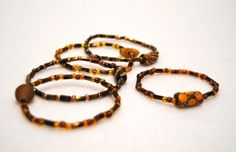Ghana Art Bead Bracelet - These beautiful recycled glass bead bracelets have variations of amber and gold seed beads and at least one handmade recycled glass art bead.  Elastic cord makes them easy to wear for any wrist. $4.00