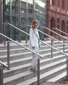 outfit deutsche fashionbloggerin mit lockigen haaren weißer lockerer hose und weißem biker mantel