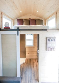 There is a barn door leading into the bathroom where you'll find a stainless steel shower, washer/dryer combo, and two cabinets.