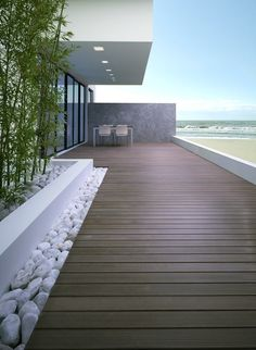 Simple but beautiful dark decking contrasting with white beach pebbles.