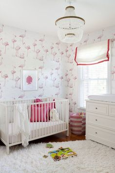White and pink nursery features walls clad in Cole & Son Flamingos Pink/White Wallpaper framing white crib dressed in white and pink geometric crib bedding, hot pink shams and velveteen rabbit as well as white pom pom fringed throw beside pink striped hamper basket and 4 drawer changing table flanked between windows dressed in pink grosgrain roman shades illuminated by beaded chandelier.