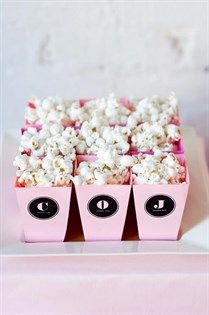 Personalized miniature boxes of buttery popcorn continue the theme of the couple's initials.