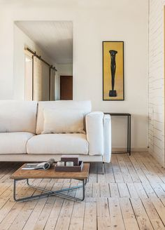 shiplap walls and rustic floorboards | yellow graphic art | IKEA Nockeby sofa with a Bemz cover in Eggshell Zaragoza velvet | simple wooden coffee table | sliding farmhouse doors in the background | scandinavian style rustic interior