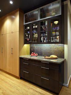 Dark wood cabinets with glass doors are used to showcase the drinkware in this contemporary kitchen. The adjacent light wood cabinets and light wood floors provide contrast in this chic space.