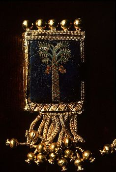 Tombs of Nimrud, Iraq.    Neo-Assyrian Empire - 9th C. B.C.E.  Gold framed pendant with semi-precious stone inlay of palm tree with dates and gold pomegranate tassles. Baghdad museum in Iraq.
