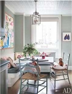 eat-in kitchen banquette, mixed chairs, abstract art, soft palette, eclectic style