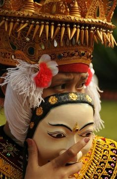 Man peeking out from behind the mask of his traditional Balinese costume.