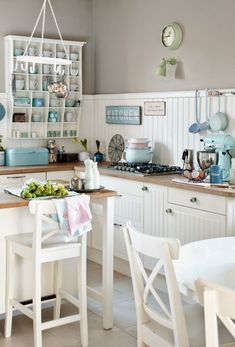 What a fresh take on the white country kitchen! Love teh greige upper wall and white beadboard backsplash. :)