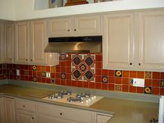 decorative Mexican tile backsplash.  I like the idea of a big design or theme for the area behind the stovetop, with small elements of design elsewhere along the backsplash.  Maybe not exactly (or as many) as shown here, but it's just an example.  I do like the colorful mexican tiles, though.