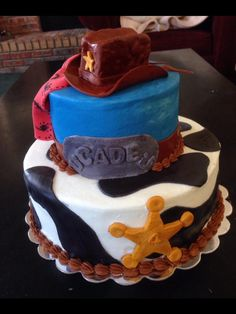 Cowboy cake. Fondant hat, cow print & star badge.
