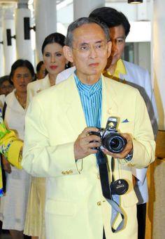 Thai King Bhumibol Adulyadej holds a camera as he walks into Siriraj hospital in Bangkok Thailand Thursday July 20 2006 King Bhumibol will undergo an...