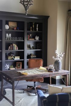 A Home Office With Grey Desk Bookcases And Swivel Chair White Cotton Cover