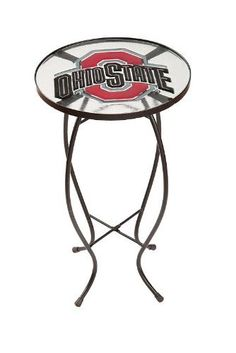 """Ohio State University Glass Table by Fans With Pride. $29.99. 12""""W x 22""""H. Embossed, painted glass top. A perfect gift for a true fan. Scarlet and grey. Black painted metal frame. Why not add a touch of Buckeyes pride into your indoor or outdoor Decor? Perfect for showing off your Ohio State passion to every friend and neighbor who stops by, this glass table is eye-catching and fun, ready for game day or any other day of the year. This could easily become your ..."""