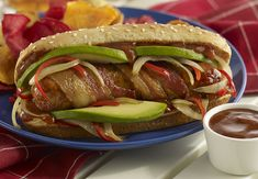 Chicken Italian sausage wrapped in bacon and grilled. Served with Spicy BBQ sauce, hot Fresno chiles and onions, cooled with creamy Fresh California Avocados on a whole wheat bun.
