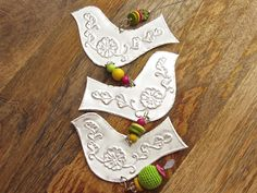 This hanging decoration of three metal birds would look beautiful as part of your nursery decor. It is made of lightweight aluminium foil and the birds are embossed in the style of Mexican tin foil art. The embossed flower pattern is similar to that used in Indian henna design. Strung between the birds are bright beads of lime green, yellow and fuchsia pink. Each bird is individually hand cut and hand embossed by me. I use hand tools only, so I create each impression by marking out the…