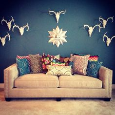 Living room-painted white deer skulls, rooms-to-go sofa with custom pillows by Dawn Laughlin