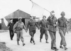 Blindfolded German officers are led back to their own lines under white flags after a talk with officers of the 9th Infantry, 2nd Division, who are fighting near Brest, France. The Germans sent an Army major, Navy captain, and a Marine chief petty officer to the Yank lines for a conference. August 19th, 1944.