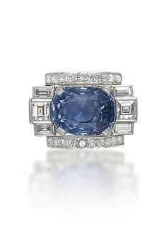 AN ART DECO SAPPHIRE AND DIAMOND RING  The cushion-shaped sapphire flanked with square and baguette-cut diamonds, to the brilliant-cut diamond line detail, mounted in platinum, 1930s