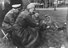 Reichsfuehrer-SS Heinrich Himmler smokes a cigar on the grass with Reinhard Heydrich and two other officers during a trip to Estonia.