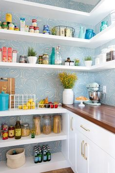 Perfectly organized blue and white kitchen pantry is fitted with white wraparound floating shelves mounted on a wall covered in Farrow & Ball Tourbillon Wallpaper over white lower shelves fixed adjacent to white cabinets adorning brass pulls and a wood countertop.