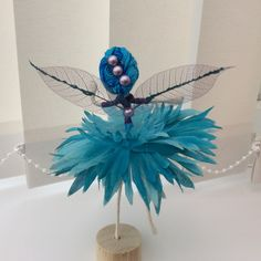 Moyà is a Flower Fairy.  Moyàs favourite colour is blue! Moyà is wearing a blue and purple variegated bodice which complements her turquoise blue spider gerbera skirt. Moyàs hair is worn up and decorated with pearls and her gossamer like wings have added fairy dust. Moyà is in a small wooden stand from which she is easily removed and will sit, stand or fly (although you may have to help her with this)! She is great for imaginative play too. Moyà is unique although she does have si...