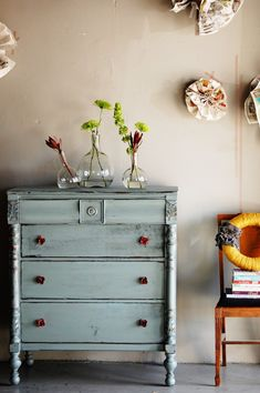 I love the blue of the dresser, the simple green plants and that lovely orange wreath! just lovely!