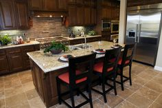 Large marble topped island with dining space centers this kitchen over beige tile flooring, with dark wood cabinetry sandwiching layered tile backsplash.