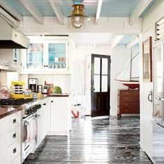 Graphic Floors: bold black-and-white faux bois treatment on this kitchen floor looks almost too pretty to walk on. The hand-painted pattern takes the traditional wood floors from standard to striking | CoastalLiving.com