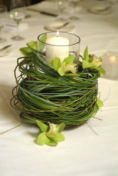 LOVE this idea!!! Swirls of bear grass and a few mini cymbidium orchids surround the tall cylinder and candle.