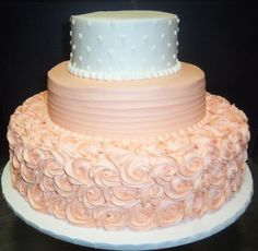 Pale peach and white three tier cake with roses, lines and dotted tiers.