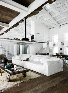 white couch white loft dark wood floors